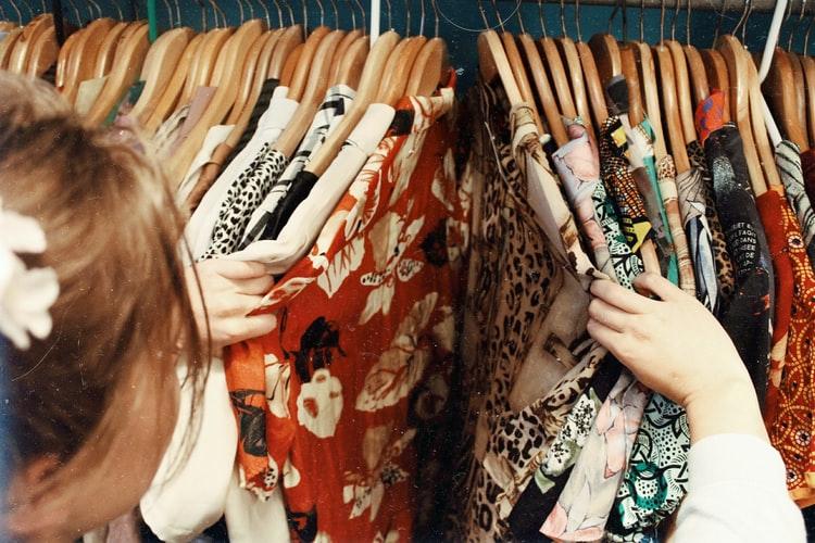 mulher escolhendo roupas na arara
