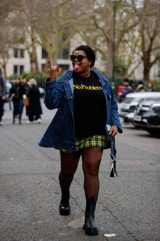 look de mulher gorda e negra com casaco jeans, camiseta e saia xadrez